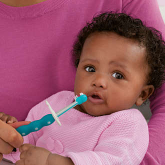 Mother holds a baby in her arms and cleans its teeth using the MAM Training Brush in Turquoise