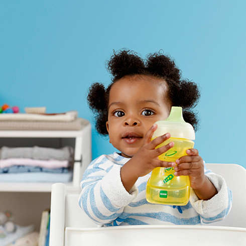Baby girl sits in a high chair and holds a yellow MAM Sports Cup in her hand