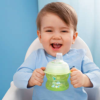 Laughing baby boy sits in a high chair with a green MAM Starter Cup in his hand