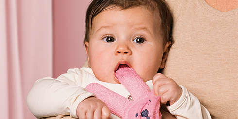 Mother cleans her baby's mouth using the MAM Oral Care Rabbit in Pink