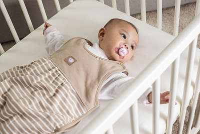 A baby has a pink MAM Start soother in its mouth and lies on its back in a cot