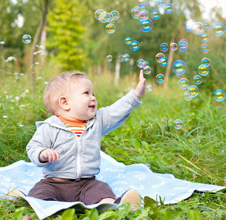 A baby boy sits in a green meadow playing with soap bubbles
