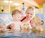 Mother swims in a pool with two toddlers at the thermal baths