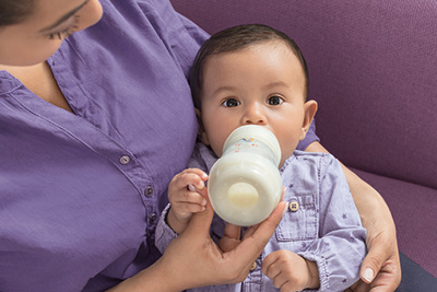 Mother sits on a couch and feeds a baby from a white MAM Easy Start Anti-Colic bottle