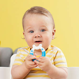 Blond baby boy holds a blue MAM Bite & Brush teether in his hands