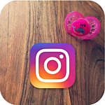 A pink MAM Original soother with a whale design lies on a wooden surface next to an Instagram logo