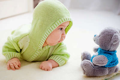 Baby aged about 5 months looks curiously at a cuddly toy