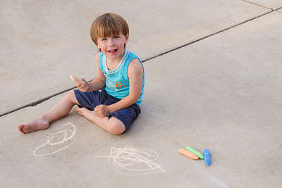 Boys draws on a concrete floor with coloured chalks