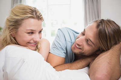 Man and woman lie in bed smiling at one another