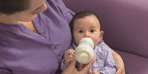 Mother sits on a couch and feeds a baby boy from a white MAM Easy Start Anti-Colic bottle