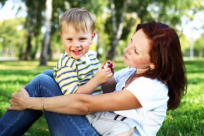 Happy mother sits with her little boy in a meadow