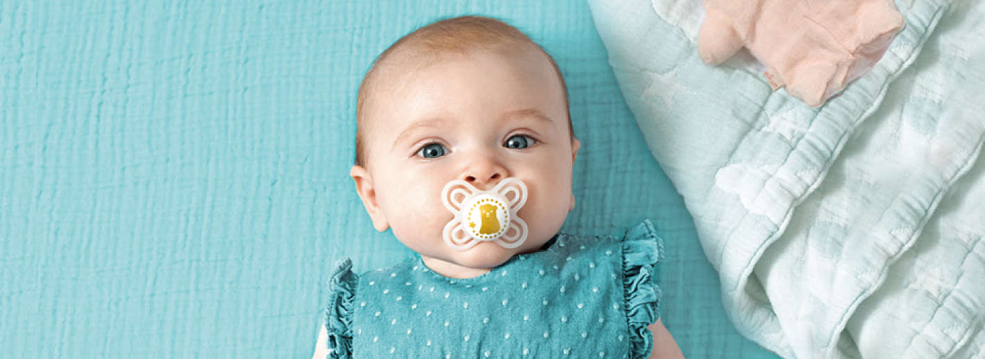 Baby lies on turquoise blanket with a white MAM Perfect Start soother in its mouth