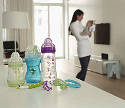 Various MAM products on a table - in the background a mother and her baby in the living room