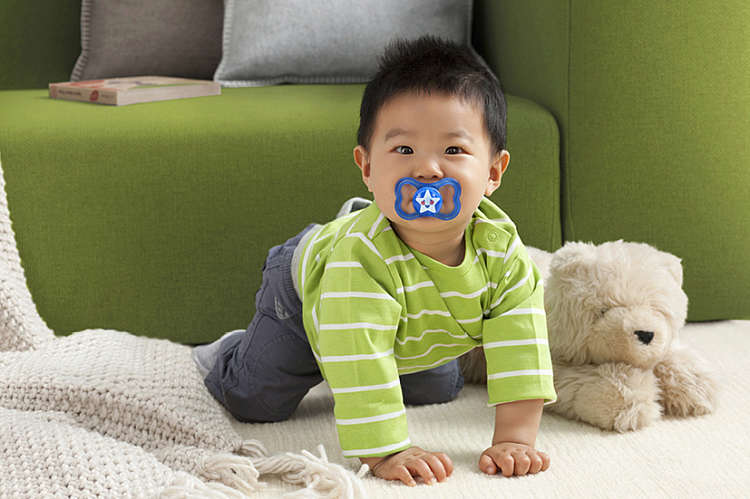 Baby boy crawls on the floor with a blue MAM Air 6+ soother in his mouth