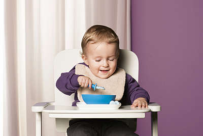 Baby boy sits in a high chair and eats puréed food using the MAM Dipper Set