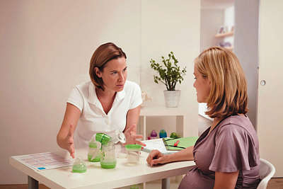 Pregnant woman is shown MAM products by a medical expert