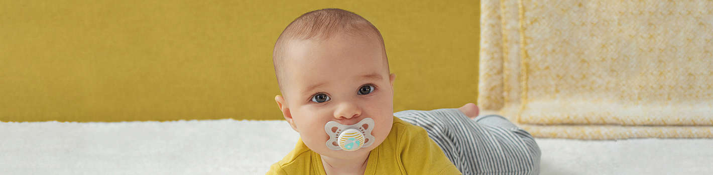 Baby lies on its tummy, lifts its head and has a grey MAM Original soother in its mouth