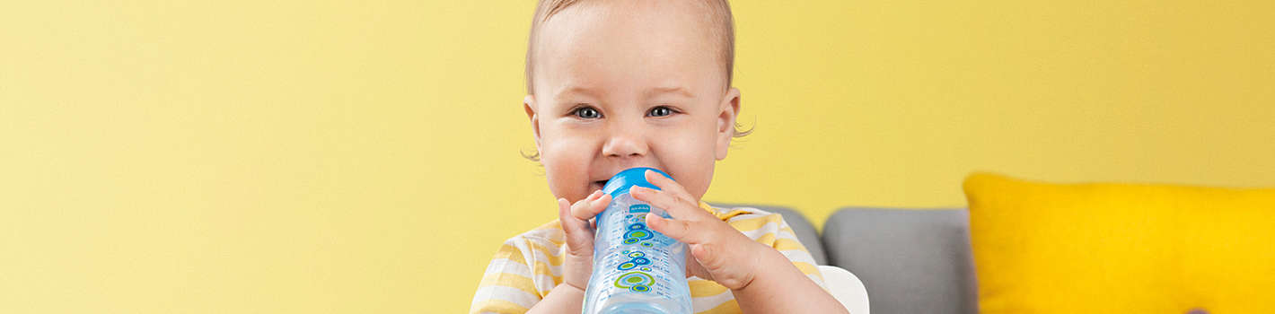 Happy baby boy drinks from a blue MAM Easy Active bottle