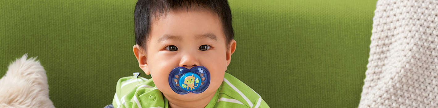 Baby boy has a blue MAM Original soother featuring a monkey design in his mouth