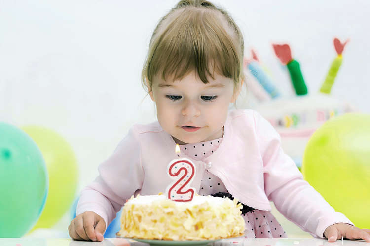Baby girl celebrates her second birthday with a cake
