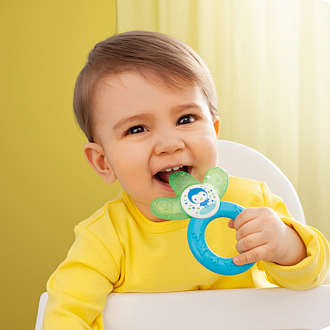 Baby boy sits in a high chair with a MAM Cooler teething ring in Green and Blue in his mouth