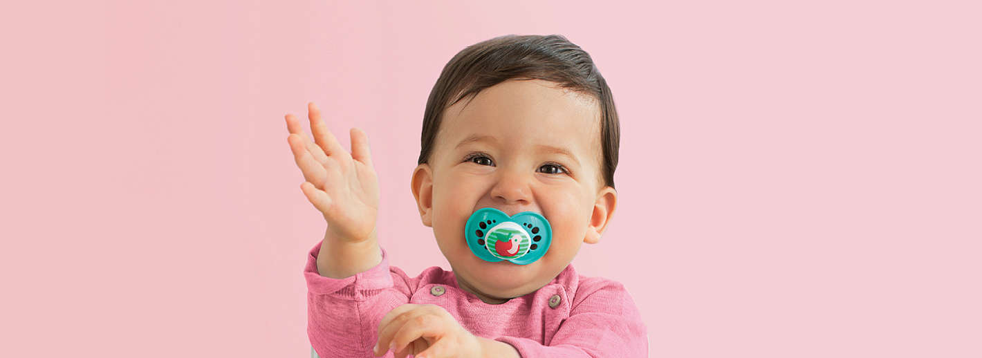 Happy baby laughs and has turquoise MAM Original with apple design in its mouth