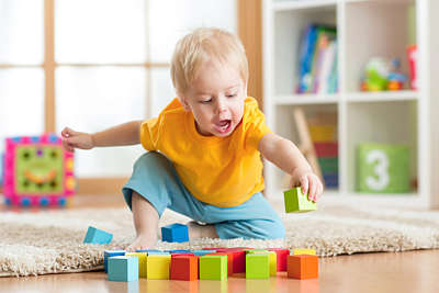 Baby boy with blond hair plays with coloured wooden blocks in a playroom