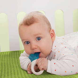 Baby in cot lies on its tummy with a MAM Mini Cooler teether in its mouth