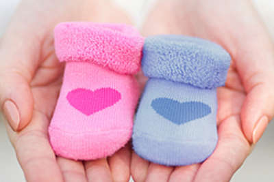 Someone holds one pink baby sock and one blue baby sock in their hands