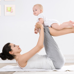 Mother doing exercise together, holding baby up with  legs