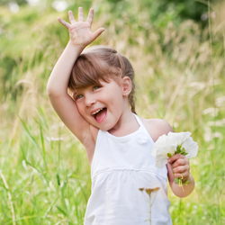 Young girl waving in a garden holding some flowers