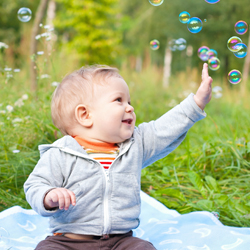 Baby boy sitting outdoors playing with soap bubbles