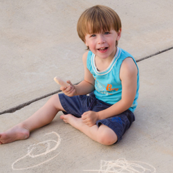 Young boy sitting on sidewalk drawing with chalk
