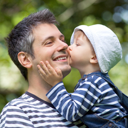 Son kissing his father on the cheek while standing  outside