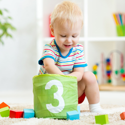 Young boy playing with wooden block toys at home