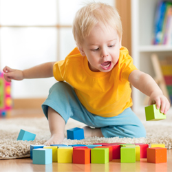 Young boy playing with wooden blocks on floor at home