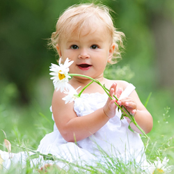 Baby girl sitting on green grass holding a flower