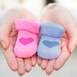 Pregnant woman holding little baby socks