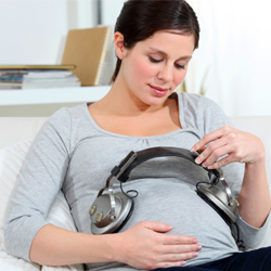 Pregnant woman putting heaPregnant woman holding  headphones on her belly music for babydphones on her belly