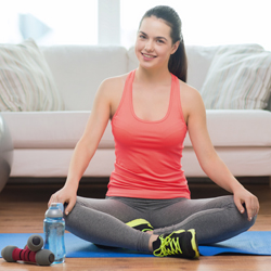 """Pregnant woman in sports gear  sitting on mat at home training in front of couch"""