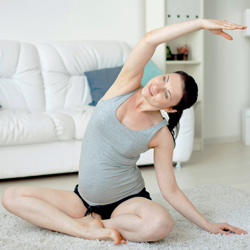 """Pregnant woman performs yoga poise  at home in her living room"""
