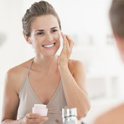 Pregnant woman applying  facial care on her face looking in mirror