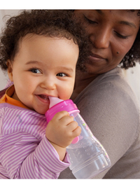 Baby girl drinks from a MAM Easy Active bottle, while being held by her mother